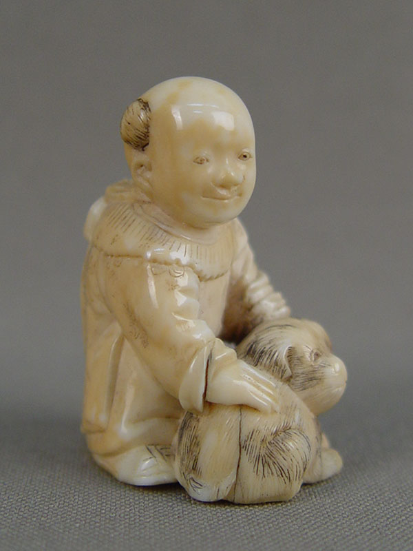 Нэцкэ «Мальчик ссобакой», кость, резьба. Япония, XIXвек, высота— 4см