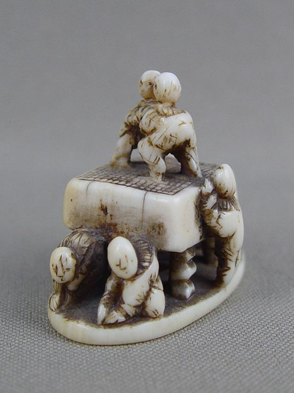 Нэцкэ «Человечки, взбирающиеся надоску для игры вГо», кость, резьба. Япония, XIXвек, высота— 4см