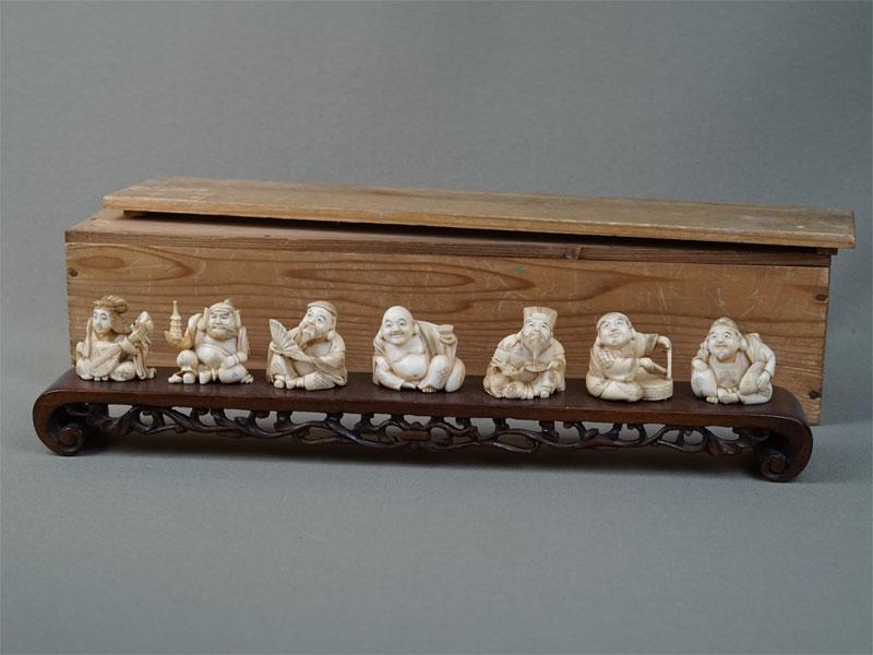 «Семь Богов Счастья» вдеревянном футляре, кость, резьба, подставка дерево. Япония, конец XIX — начало XXвека, длина подставки 24см, высота фигурок 3см