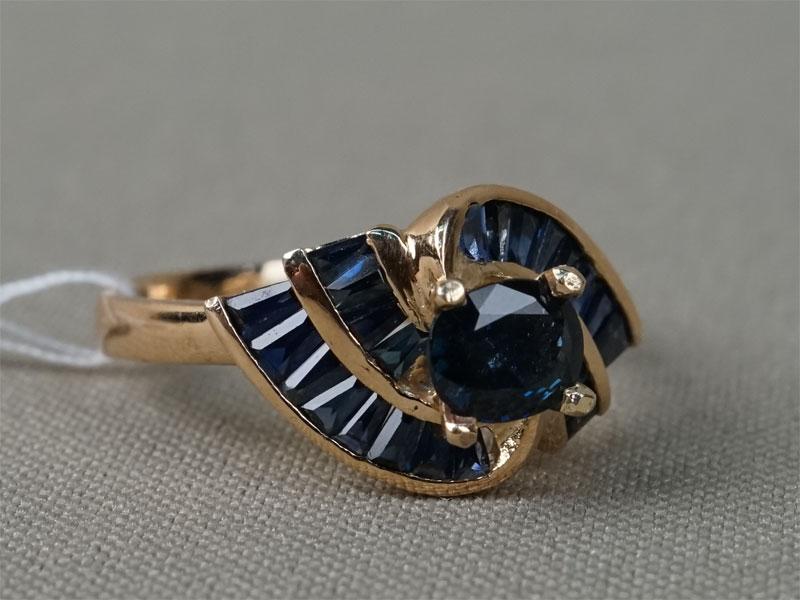 Кольцо, золото 585пробы, общий вес— 4,02г. Вставки: 1сапфир («Овал» — 0,62ct 2/4; 24сапфира («Багет» — 0,87ct 2-3/3). Размер кольца 18.