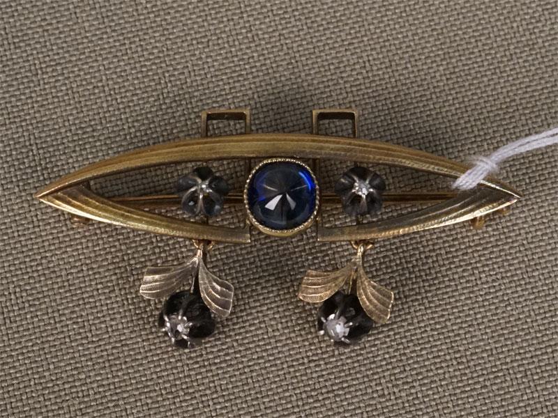 Брошь в стиле ар-деко, золото 56пробы, вставки: бриллианты (2бр «старой» упрощенной огр. 0,013/3, 2бр «роза»), сапфир (1сапф. «кабошон» 0,803/3), общий вес— 4,81г.