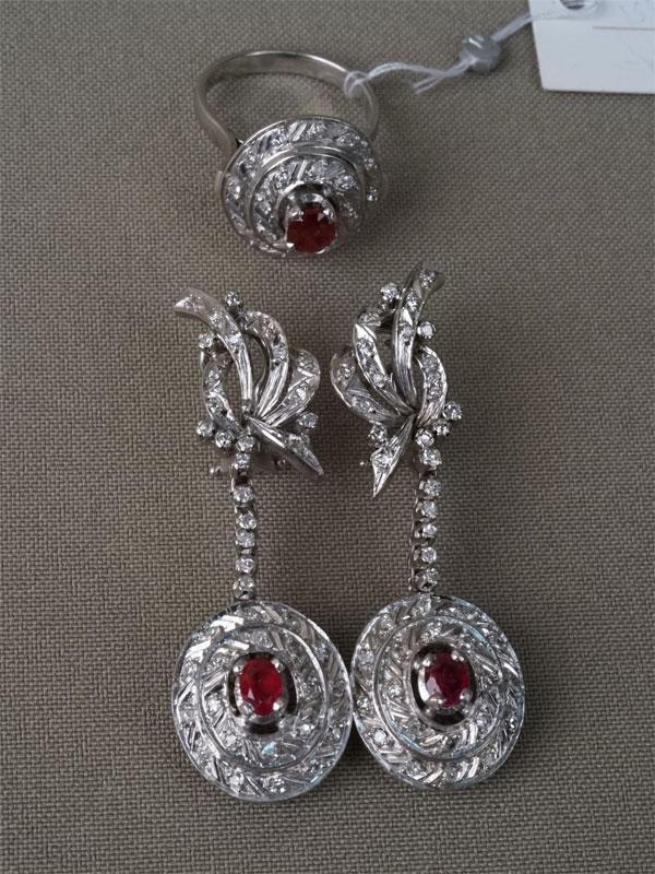 Комплект: серьги и кольцо, золото 585 пробы, общий вес 15,96г. Вставки: 106 бриллиантов (Кр17 – 1,45ct 3/4-6); 3 рубина («Овал» — 1,40ct 2/4). Размер кольца 17