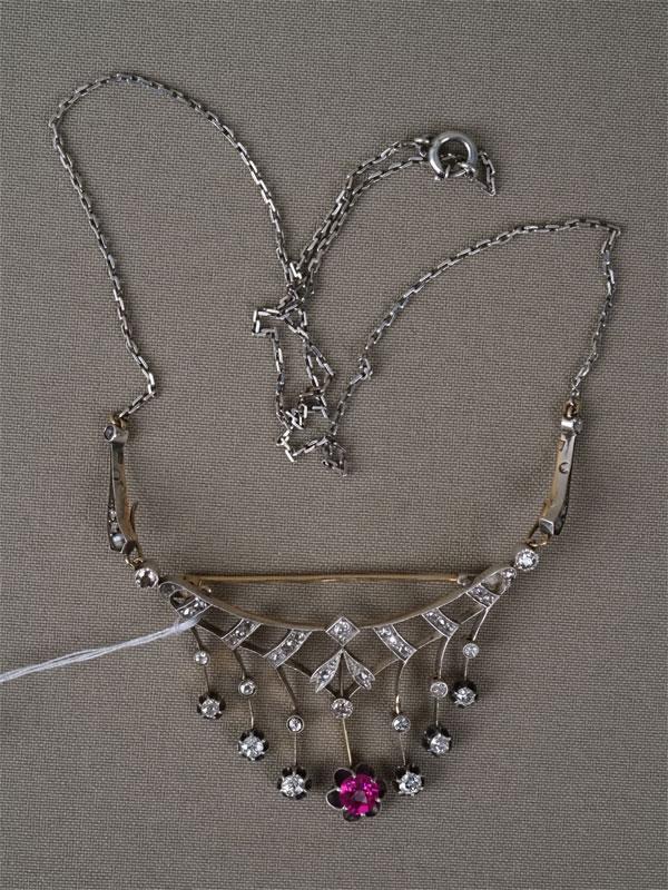 Колье-брошь, золото 56 пробы, вставки: бриллианты (17 бр. «старой» упрощенной огр. 1,34 3/3-4, 27 бр. «роза»), выращенный рубин; общий вес 13,36г.