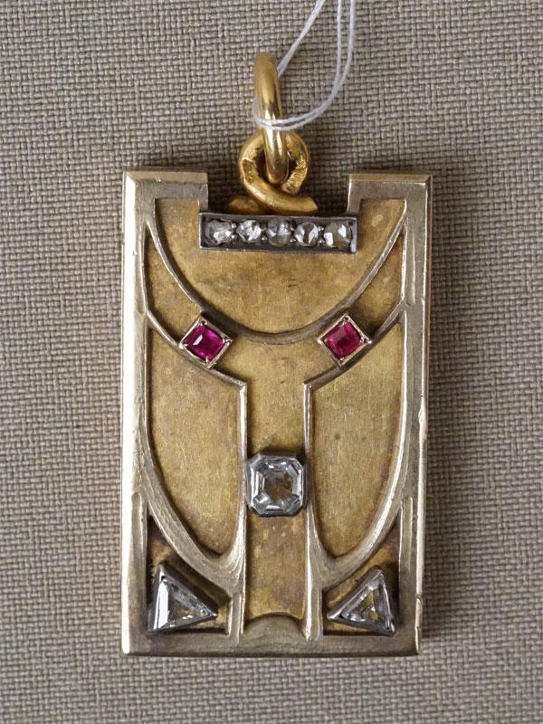 Подвеска-медальон в стиле модерн, золото 56 пробы, общий вес 19,20г. Вставки: 3 бриллианта (2 «Треугольной» огр., 1 «Октагон»); 2 рубина природных («Багет»); 5 бриллиантов («Роза»)
