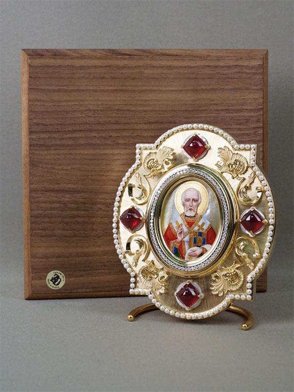 Икона «Святой Николай Чудотворец» в футляре, золото 750 пробы, общий вес 345,5г. Вставки: бриллианты (80бр Кр57 – 3,61ct 3/5-6), 4 природных облагороженных рубина (101,88ct), культивированный жемчуг. Подставка серебро по реактиву, золочение. 14х12см. Атрибуция.