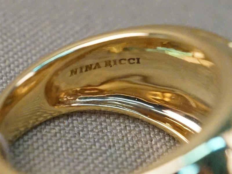 Кольцо Nina Ricci, золото 750 пробы, общий вес 11,32г.  Размер кольца 18,0. Вставки: 1 сапфир («Круг» — 0,15ct 3/4); розовые, желтые и зеленые сапфиры.