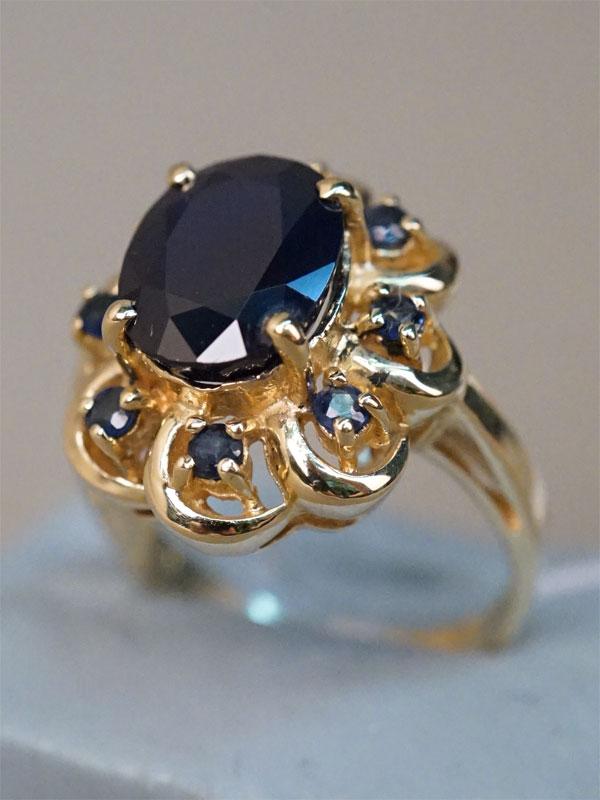Кольцо, золото по реактиву (14К), общий вес 5,55г. Вставки:  сапфиры (1 сапф. «Овал» — 3,10ct 5/5; 8 сапф. «Круг» — 0,30ct 3/3). Размер кольца 16.