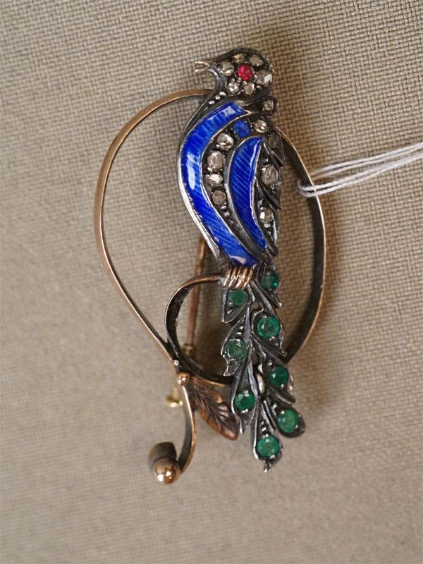 Брошь «Птица», золото по реактиву, вставки: изумруды (8 из «круг» 0,32  2-3/г3), рубин (0,03 3/3), бриллианты «роза» (15 шт), выращенная синяя шпинель; общий вес 6,49г.