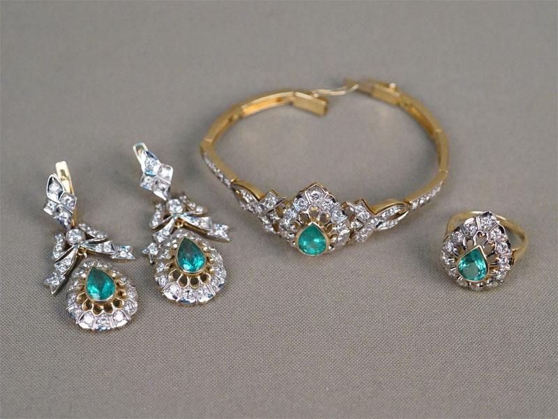 Комплект: серьги, кольцо и браслет, общий вес 50,25г. Вставки: браслет – бриллианты (55бр Кр57 – 2,48ct 4/4-5); 1 изумруд («Груша» — 1,90ct 3/Г2); кольцо -бриллианты (13бр Кр57 – 1,03ct 4/4-5); 1 изумруд («Груша» — 1,62ct 3/Г2); серьги — бриллианты (2бр Кр57 – 0,30ct 4/5; 62бр Кр57 – 1,44ct 4/4-5); 2 изумруда («Груша» — 3,43ct 3/Г2)