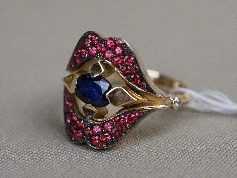 Кольцо «Алые губки», золото 585 пробы, общий вес 7,14г. Вставки: 1 сапфир («Овал» — 0,50ct 2/3); 2 бриллианта (Кр57 – 0,03ct 4/6); 42 пурпурных сапфира (0,85ct). Размер кольца 18,5. Экспертиза.
