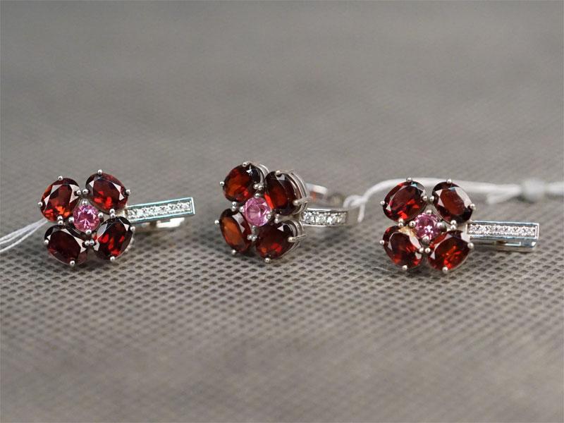 Комплект: серьги и кольцо, золото 750 пробы, общий вес 14,80г. Вставки: 22 бриллианта (Кр57 — 0,19ct 3-4/4-5); 12 гранатов («Овал»); 3 розовые шпинели («Круг»). Размер кольца 17,5