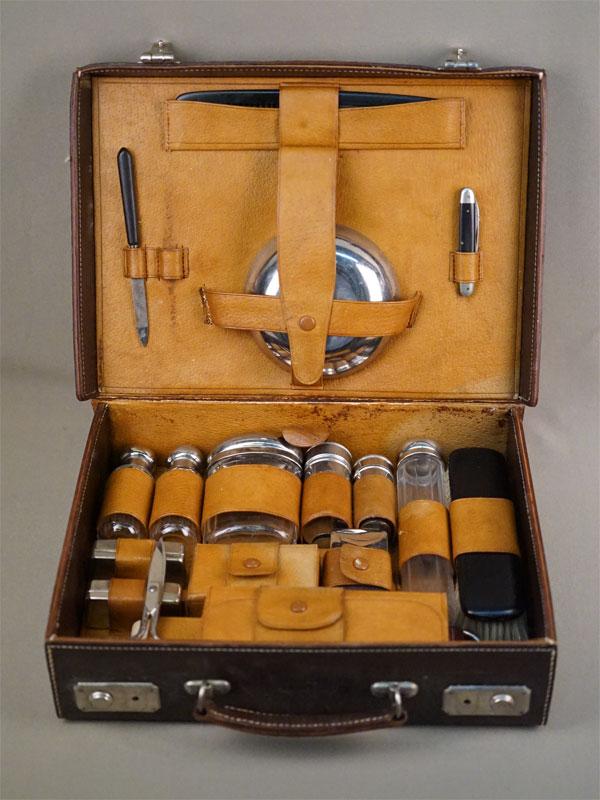 Дорожный несессер в чемоданчике (18 предметов), металл, стекло, кожа, первая половина XX века, 25 × 33см