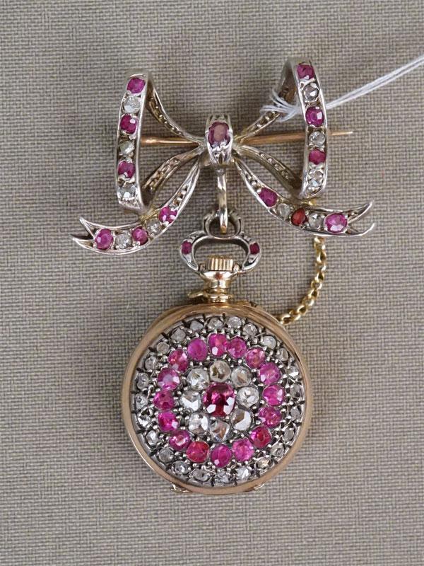 Брошь-часы «Бант», золото по реактиву, общий вес 20,12г., высота 5,5см. Вставки: бриллианты («Роза»), розовые сапфиры, гранат, красный дублет.