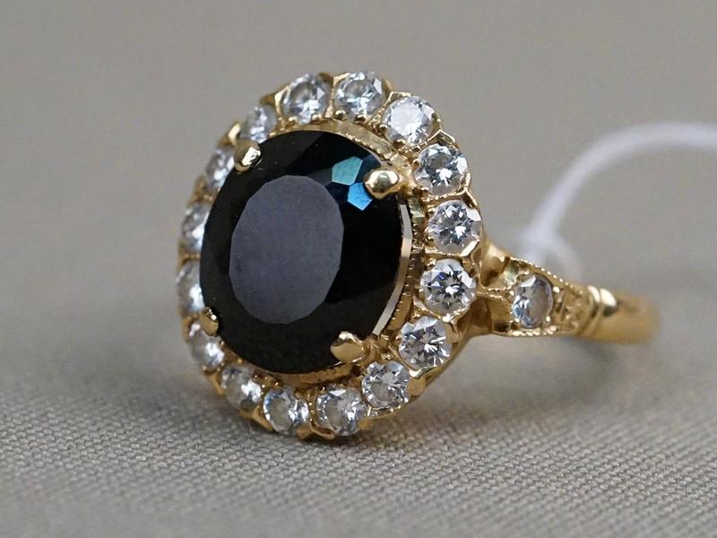 Кольцо, золото по реактиву, общий вес 5,97г.  Вставки: 18 бриллиантов (Кр57 – 1,30ct 4/3); 1 сапфир («Овал» — 5,70ct 5/3). Размер кольца 19,5.
