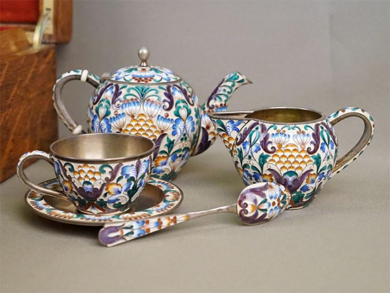 Сервиз чайный на 6 персон в деревянном футляре (24 предмета: 6 чайных пар, 6 чайных ложек, чайник, сахарница, сливочник, ситечко для чая, щипцы для сахара, вилочка для лимона), серебро 916 пробы, золочение, эмаль, общий вес 1684,5г. СССР, 1927-1955 годы, для фирмы Тиффани